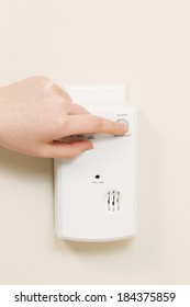 Vertical photo of carbon monoxide alarm with female hand testing the system