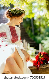 Vertical photo of charming ukrainian bride in national linen dress with a wreath on her head and red bouquet sitting on old bench Ukrainian folklore wedding, culture, ethical traditions, concept.