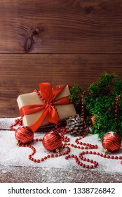 Vertical photo of a Christmas composition on a wooden background from coniferous branches, toys for the Christmas tree, cones and a gift box tied with a red ribbon with a bow