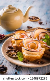 Vertical photo with crispy dessert. Sweet is made from apple slices and puff pastry. Dessert is called apple roses. Several herbs and spices are spilled around with powder sugar.