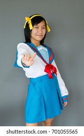 Vertical photo of cute smiling asian teenager girl in school uniform making a stop sign with her index finger raised