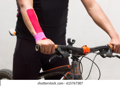 Vertical photo of a cyclist on his mountain bike with kinesio tape on his right wrist to reduce pain