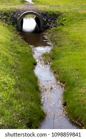 Vertical photo of ditch with gleaming stream of water and culvert under access to rural property