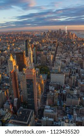 Vertical photo of the downtown Manhattan skyline at sunset as seen from the top of the Empire State building. The Freedom Tower is illuminated in the distance
