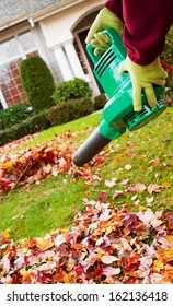 Vertical photo of electrical blower, gloved hands holding, cleaning leaves from front yard with house in background