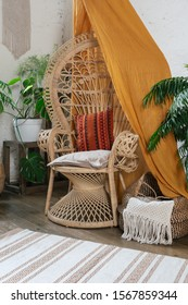 Vertical photo of elegant and comfort living room with boho style interior, rug on wooden floor, wicker chair, pillows, cushions and green plants in flower pots