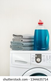 Vertical photo of finished laundry process. White washing machine with bottle of detergent liquid on top standing against wall inside flat with bright interior