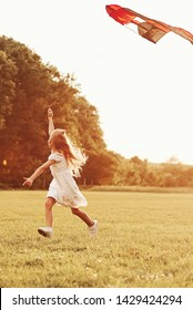 Vertical photo. Happy girl in white clothes have fun with kite in the field. Beautiful nature.