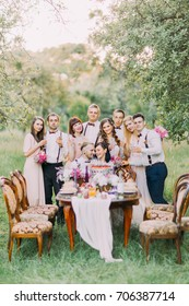 The vertical photo of the happy newlywed couple and the smiling guests standing behind them at the background of the spring green field.