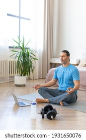 Vertical photo. Meditation practice - middle aged man during online yoga steaming. A man sits on a yoga mat in front of a laptop monitor and meditates.