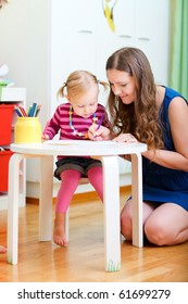 Vertical photo of mother and daughter drawing together