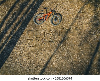 """Vertical photo of a mountain bike lying in a forest floor covered with leaves and writing """"ostanite zdravi"""" or """"stay healthy"""". - Shutterstock ID 1681206394"""