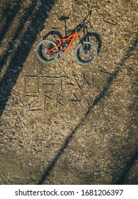 """Vertical photo of a mountain bike lying in a forest floor covered with leaves and writing """"ostanite zdravi"""" or """"stay healthy"""". - Shutterstock ID 1681206397"""