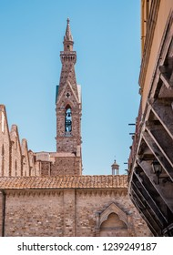 Vertical photo with narrow and high tower with bell in famous Italy city Florence. City is in Tuscany. Sky is blue without clouds. Few ancients buildings from bricks are in foreground.