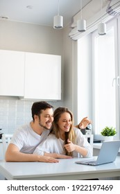 Vertical photo - online meet with relatives or friends. Happy smiling couple during online video call in front of laptop monitor.