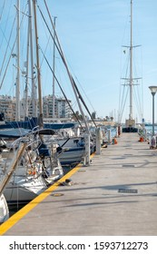 Vertical photo of pier with moored sailing boats in port. Maritime walking. Balearic islands, Majorca. High class lifestyle. Yachting sport. Luxury summer vacation. Marina with anchored yachts.
