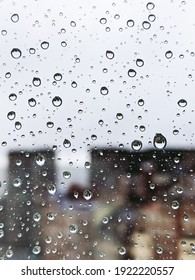 Vertical photo of raindrops on a glass with silhouette of buildings out of focus in the background