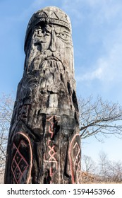 Vertical photo of Slavic god Perun carved on a wooden pillar, a pagan idol close-up on a background of blue sky - Shutterstock ID 1594453966