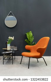 Vertical photo of soft chair made from orange color textile standing near small table with flowers in living room interior