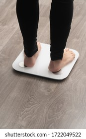 vertical photo space bare feet in black leggings on the scales on light background back view. summer season weight loss concept.