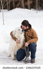 Vertical photo of sturdy brown-haired young man kneeling on icy countryside road to pet his huge Pyrenean Mountain Dog looking up with happy expression
