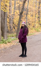 Vertical photo of sultry hispanic young woman with long flowing curly dark hair standing in dirt road wearing warm casual clothes in front of soft focus Fall foliage