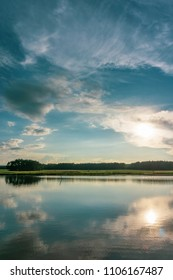 Vertical photo with summer landscape. Small pond is in foreground with reflected blue evening sky full of dramatic clouds. Green meadow with trees is in background.