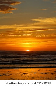 A vertical photo of sunset on the beach, black waters and golden sun.