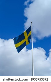 A vertical photo of the Swedish flag against the cloudy sky. Blue and yellow symbol of patriotism in Sweden