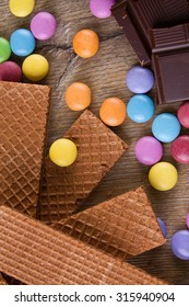 Vertical photo with top view on several colorful chocolate sweets on wooden board together with broken pieces of dark chocolate and few chocolate biscuits.