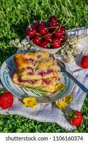 Vertical photo with two portions of cherry cake. Cake is placed on saucer and on white towel. Bowl full of other fruits is next to cake with several red strawberries and blooms.