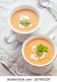 Vertical photo of two white cups with vegan (vegetarian) pumpkin cream soup with coconut milk, served with parsley. Rustic tablecloth in the background, silver spoons on the side. Elevated view.