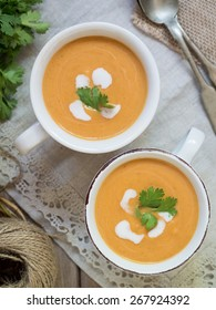 Vertical photo of two white cups with vegan (vegetarian) pumpkin cream soup with coconut milk, served with parsley. Rustic tablecloth in the background, silver spoons on the side. View from the above.