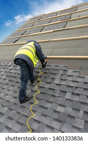 Vertical photo of unrecognizable roofer worker in uniform work wear using air or pneumatic nail gun and installing asphalt or bitumen tile on top of the roof under construction house