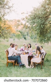 The vertical photo of the wedding dinner with the newlyweds and guests celebrating the ceremeny in the sunny forest.