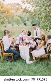 The vertical photo of the wedding dinner in the sunny wood. The newlywed couple is sitting at the table and kissing while the guests are applauding.