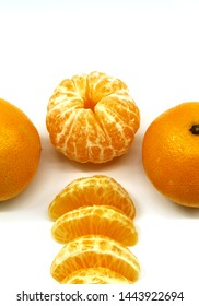 Vertical photo. White background. Orange tangerines. One piece of fruit without a peel, two with peel, slices of Mandarin