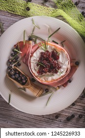 Vertical photo of whole camembert. Cheese is wrapped in dry ham and has cranberries on top. Cheese is on white plate with spilled juniper fruit around on wooden board with worn color.