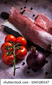 Vertical photo of whole pork tenderloin. Raw meat is on vintage wooden board with red cherry tomatoes and purple onion. Juniper berries are spilled around. Two empty bottles are in background.