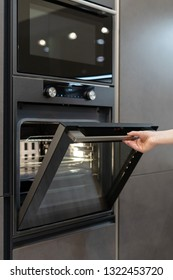 Vertical photo of woman hand opening new modern built-in oven with light inside