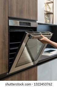 Vertical photo of woman hand opening metallic door on built-in oven in brown wooden kitchen cabinet