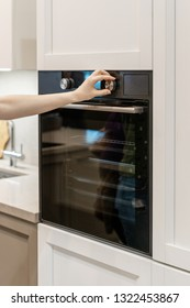 Vertical photo of woman hand tuning program on control panel for black built-in oven in white kitchen cabinet
