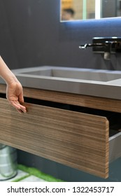Vertical photo of woman hands opened wooden drawer under sink in bathroom