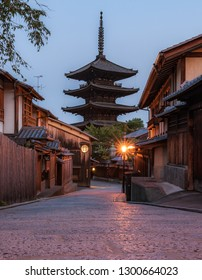Vertical photo of Yasaka Pagoda which is a five-story pagoda located to the west of Ninenzaka and Sannenzaka streets in Kyoto City's Higashiyama district, during golden hour right after sunrise.