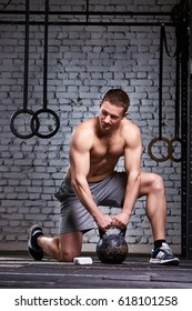 Vertical photo of young athletic man while holding kettlebell on the gym floor against brick wall.