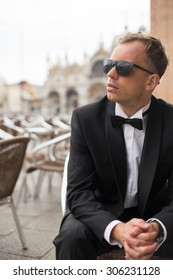 Vertical photo of young handsome man in tuxedo sitting in outdoor cafe
