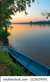 Vertical photograph of the Amazon Rainforest at sunset with a blue canoe in the foreground along the Napo river, Yasuni national park, Ecuador.