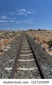 A vertical photograph of a railway train track leading into the distance in the desert of Namibia during a hot day with a few clouds in the sky.