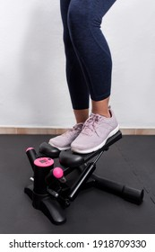 Vertical photography of woman's legs on a stepper machine. Fitness girl training cardiovascular to burn calories.