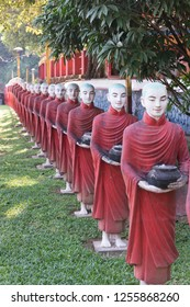 Vertical picture of aligned monks statues representing Offering at Kaw Ka Thaung Cave, located close to Hpa-An, Myanmar